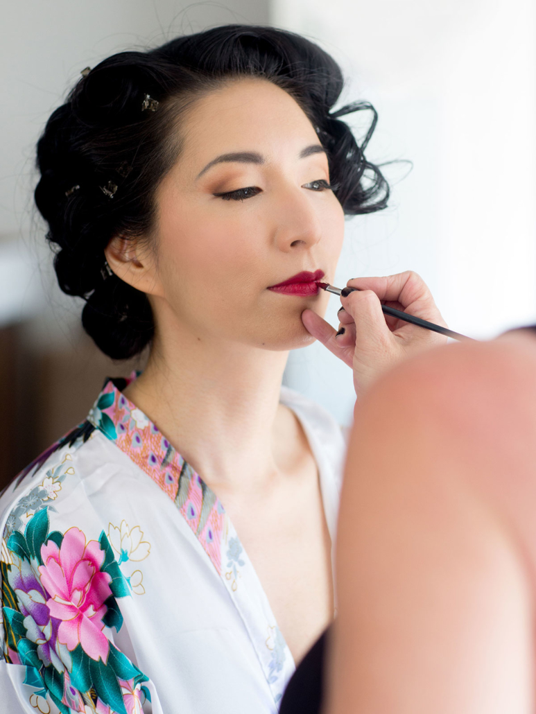 makeup artist applying makeup on an Asian Bride